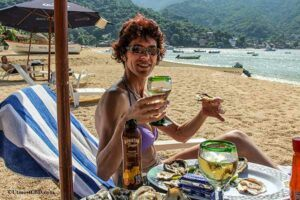 A woman is drinking wine and eating oysters on a beach while taking her sunbath